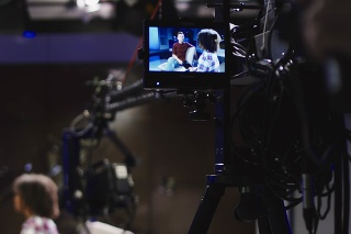 Young confident and relaxed man and woman taking participation in television show sitting in modern illuminated studio and having talk. The cameraman of the TV recording show.