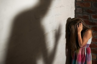 Abused little girl huddled over while the shadow of her abuser looms towards her