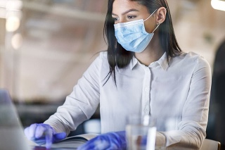 Female entrepreneur with face mask and protective gloves working on a computer during corona virus pandemic in the office. The view is through glass.