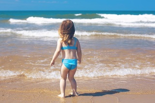 Little girl standing on the beach looking to the ocean