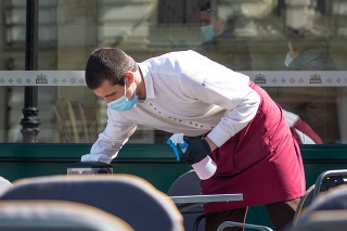 Vilnius, Lithuania - April 30 2020: Waiter with a mask disinfects the table of an outdoor bar, café or restaurant, reopen after quarantine restrictions