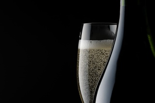 Champagne glass and blank bottle against black background with copy space.