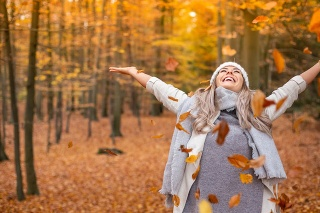 Girl walking in the park in autumn and smiles with open arms