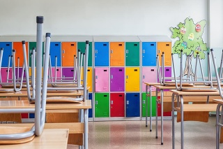 Modern emty classroom with colorful lockers and raised chairs on the tables