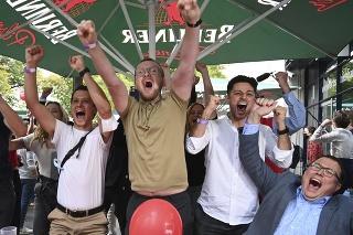 Podporovatelia Sociálnodemokratickej strany Nemecka (SPD) sa tešia po zverejnení výsledkov exit pollov parlamentných volieb v Nemecku v nedeľu 26. septembra 2021.