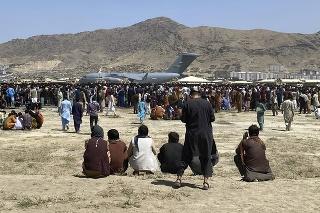 Ľudia sa zhromažďujú neďaleko amerického transportného lietadla C-17 na medzinárodnom letisku  Hámida Karzaja v Kábule v utorok 17. augusta 2021.