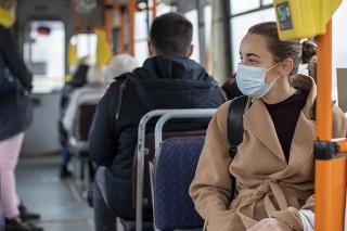 Ľudia s ochrannými rúškami na zabránenie šíreniu nového koronavírusu cestujú v autobuse vo Vilniuse.