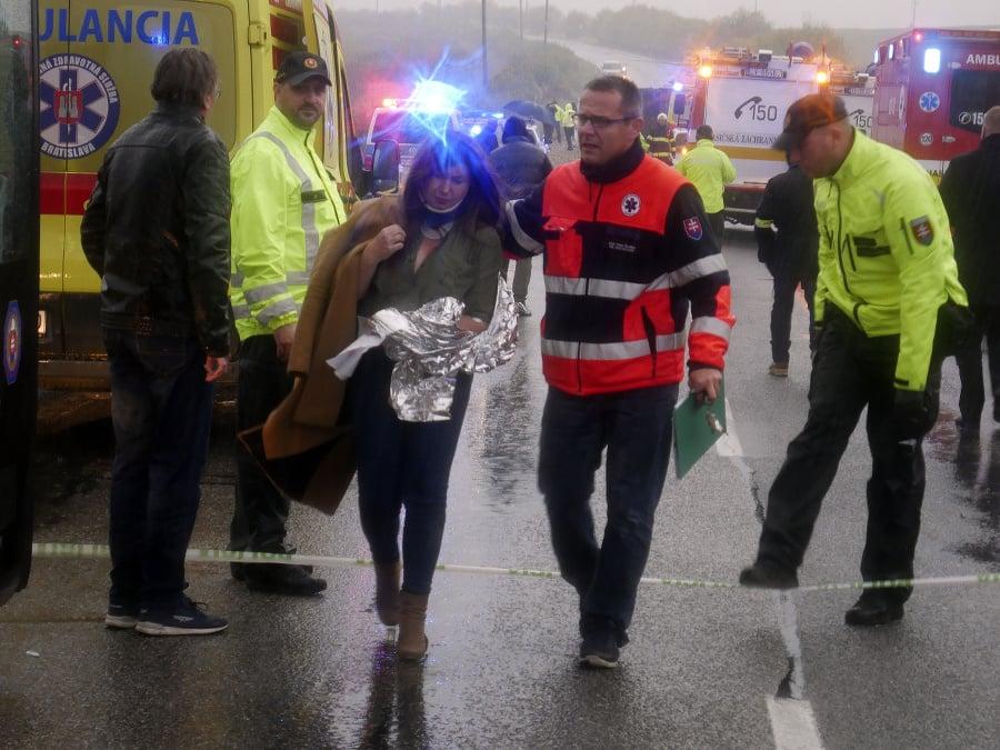 Záchranár doprevádza zranenú ženu