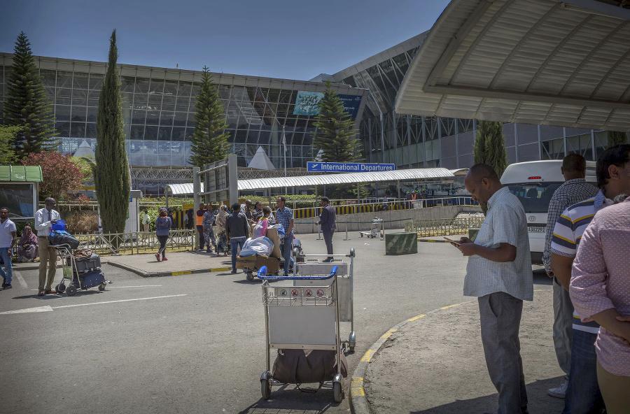 Cestujúci pred letiskom v