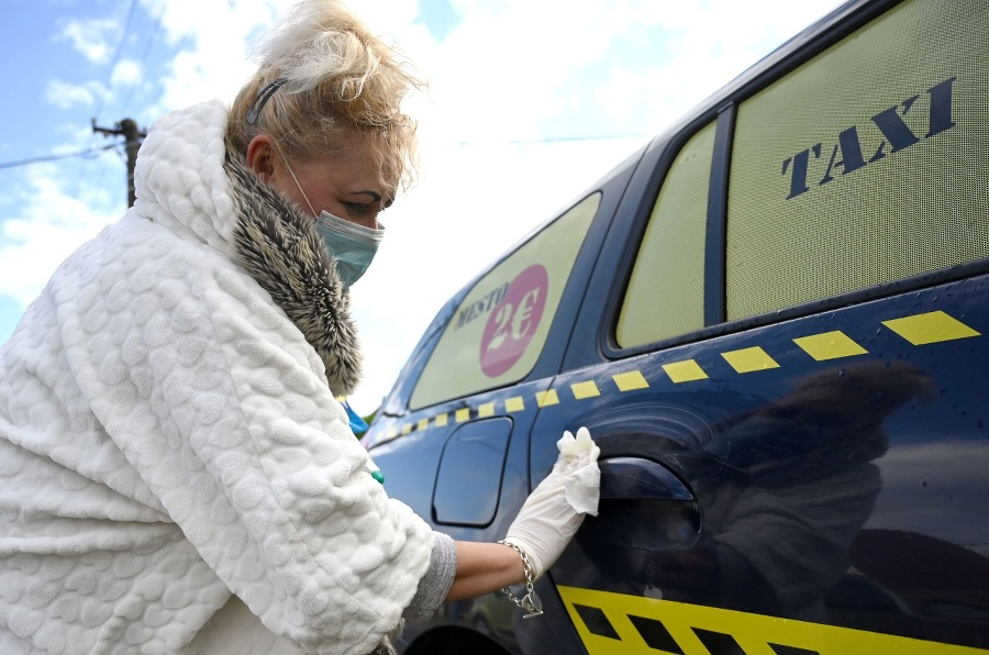 Taxikárka dezinfikuje vozidlo taxislužby