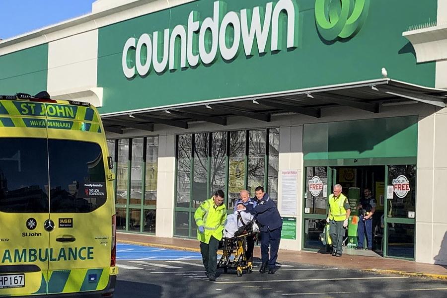 Policajti odvážajú na nosidlách zraneného muža zo supermarketu po útoku muža nožom v novozélandskom meste Dunedin.
