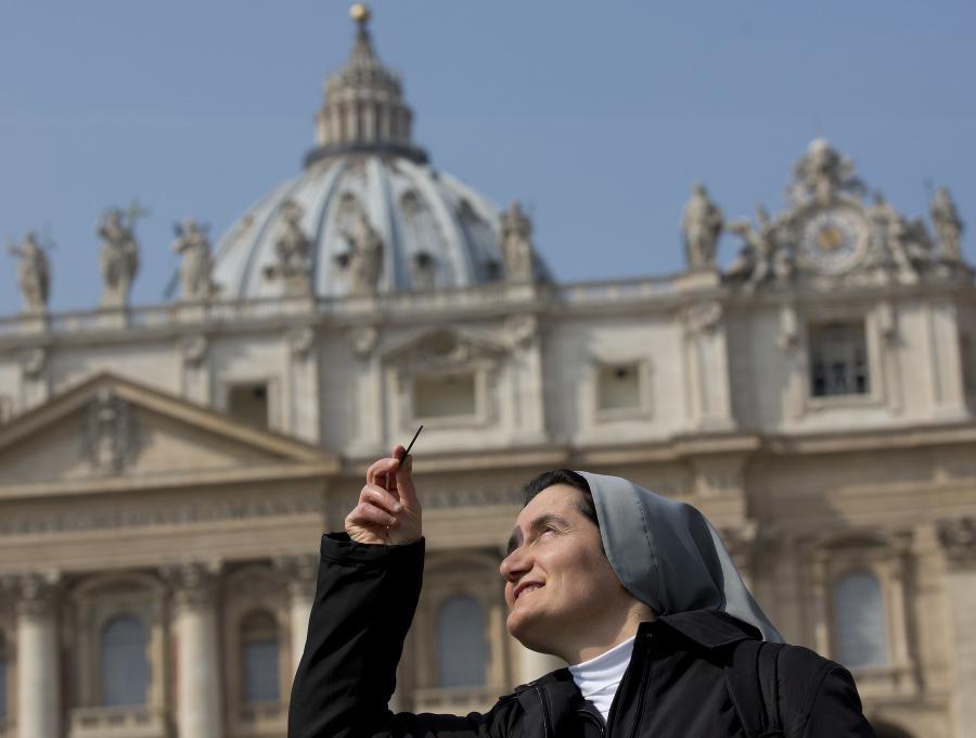 Mníška Mira z Albánska sleduje čiastočné zatmenie Slnka na Námestí sv. Petra vo Vatikáne 20.  marca 2015.