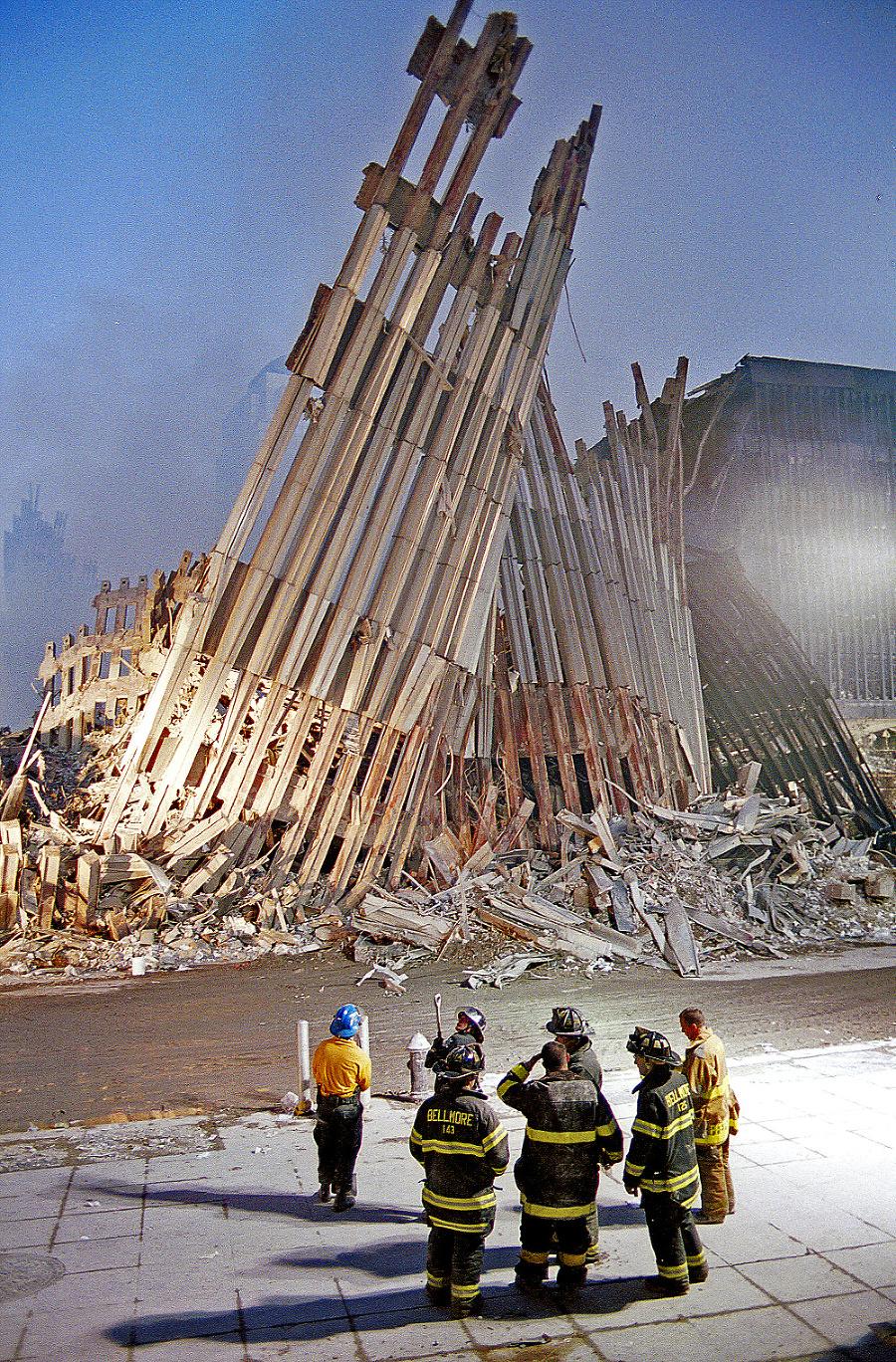 Hasiči sa bezmocne prizerajú na fasádu zrúteného Svetového obchodného centra.