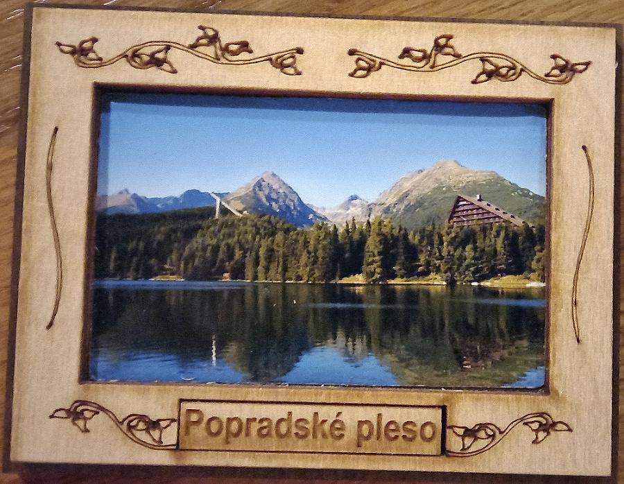 V drevenom rámčeku s nápisom Popradské pleso je umiestnená snímka Štrbského plesa.